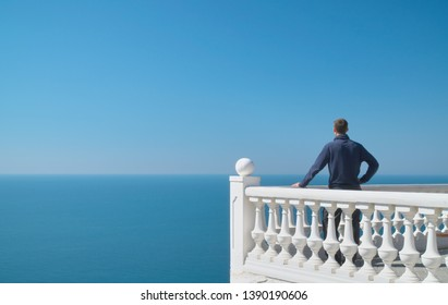 Man standing on balcony and look on the sea horizon at day. Calm and relax composition.