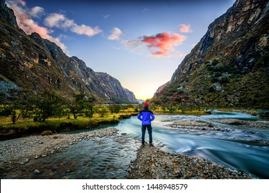 Man Standing on the banks of a River Looking at a Beautiful Mountain Valley During Sunset with a Pink Cloud - Location: Santa Cruz Trekking, Ancash, Peru, South America