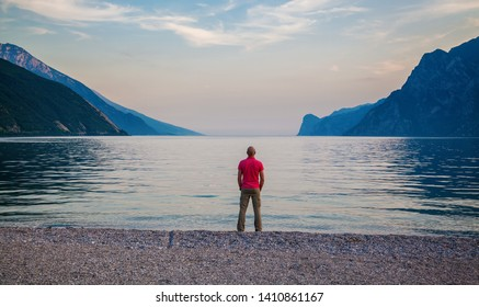 man standing on the beach of beautiful Garda lake in the evening, Italy