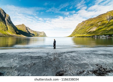 Man standing on beach by fjord in Senja norway looking out over the horizon