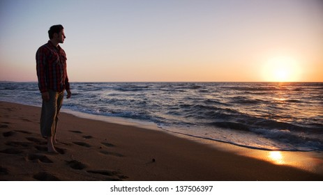 Man standing on the beach and looking into sunset, sun is disappearing into the sea - twilight scene