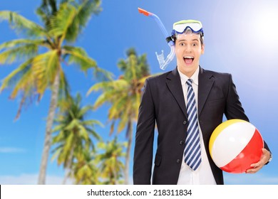 Man standing on beach with snorkel and beach ball