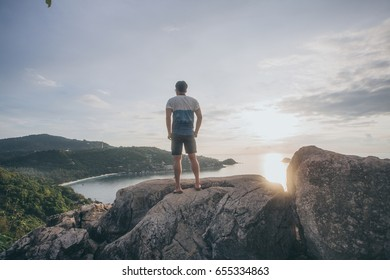 Man standing on the beach staring at Table Mountain. Alone man on the beach. Alone man on the hilltop.