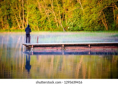 Man standing on a bridge and fishing in the lake