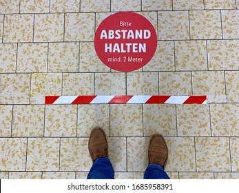 Mann, der an einem Chekout-Schalter in einem Supermarkt mit Schild steht ( deutscher Text: Bitte, Entfernung mindestens 2 Meter) - Coronavirus