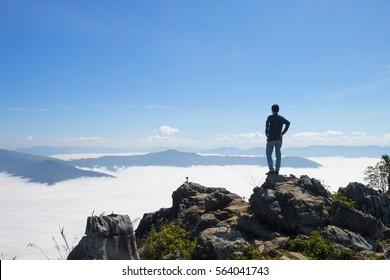 man standing on the cliff and looking at the valley and mountains in the daylight