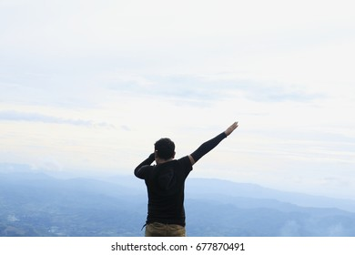 A man standing on cliff and see over view in nature. Tourist show  hands up and enjoying fresh air. A man enjoying free happiness in beautiful Thailand landscape.