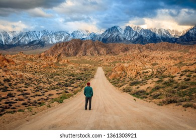 Man standing on a dirt road in the Sierra Nevada Mountains, California, USA.