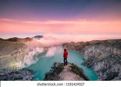 Man standing on edge of crater with colorful sky at morning. Kawah Ijen volcano, East Java, Indonesia
