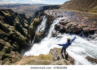 Man standing on the edge of the picturesque waterfall in Iceland