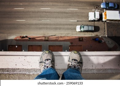man standing on edge of tall building looking down upon the road with moving cars passing by below (shallow depth of field)