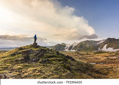 man standing on field near active volcanoes of Kamchatka with snowy hills