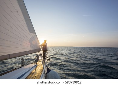 Man Standing On Front Of Luxury Yacht In Sea