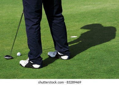 A man is standing on the green of a golf course. He is putting the ball into the hole.