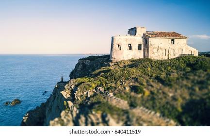 A man standing on a high cliff enjoying the view of an Italian coast with the Mediterranean sea Below him. Porto Cervo - Emerald Coast, Sardinia - Italy