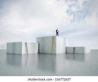 man standing on highest cube with ladders