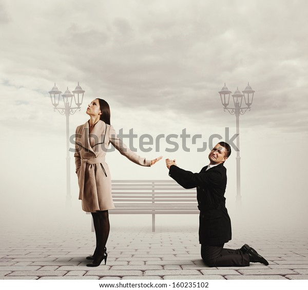 man standing on his knees and asking for forgiveness