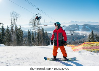 Man standing on his snowboard on a ski slope at winter resort with ski lifts visible behind on background blue sky at sunny day in the morning. Ski season and winter sports concept. Bukovel, Ukraine