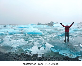 Man standing on icebergs raising hands in Jokulsarlon glacial lagoon in Iceland. Nature, holidays, freedom, travel, adventure, success concept