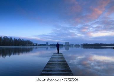 Man standing on a jetty, looking over a lake toward the city.