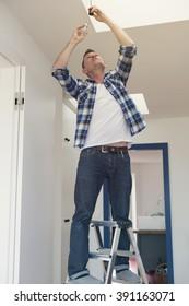 man standing on ladder changing a lightbulb