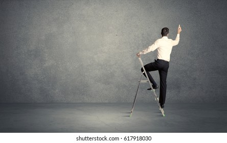 A man standing on ladder drawing with chalk in his hand on clear wall pattern background
