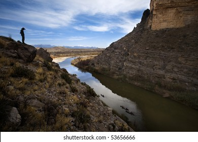 Man standing on large cliffs looking over river at canoes down in the water