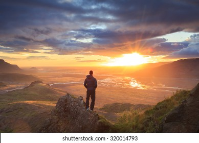 Man standing on a ledge of a mountain, enjoying the beautiful sunset over a wide river valley in Thorsmork, Iceland.