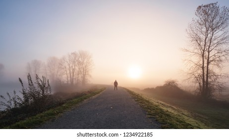 Man standing on a long gravel path with a foggy sunrise in the distance.