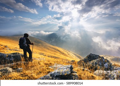Man standing on a mountain summit at sunset. Man reaching summit enjoying freedom and looking towards mountains sunset.