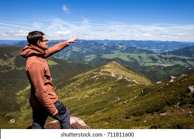Man standing on the mountain top and pointing on horizon