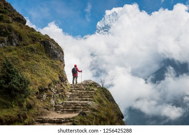 Man standing on the mountains edge and looking to Mt.Thamserku (6,623 m) behind the clouds in Khumbu region of Nepal.
