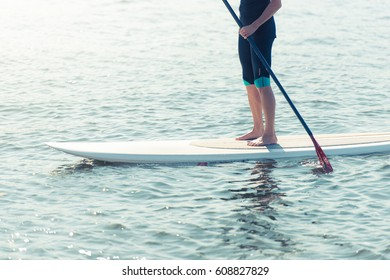 Man standing on paddleboard in water