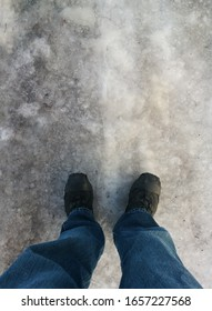 Man standing on a pathway fully covered with rough ice, with crampon on his boots, wearing jeans