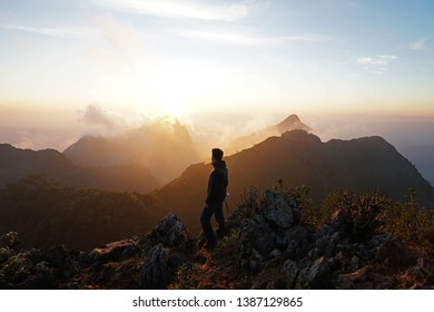 A man standing on the peak looking at green mountain range with cloudy sky