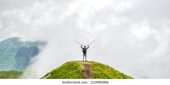 man standing on the peak of the mountain