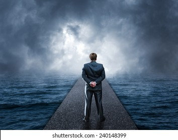 Man standing on pier looks at the sea