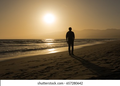 A man standing on a quiet and calm Californian beach looking at a golden sun set on the Pacific Ocean and nearby hills rolling up from the sea