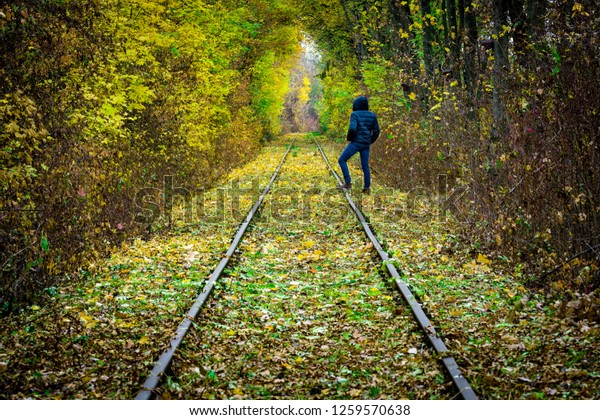 Man standing on rails surrounded by trees forming a tunnel of autumn colors leading into nowhere