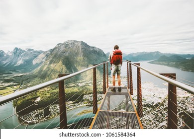 Man standing on Rampestreken viewpoint over mountains Travel Lifestyle adventure vacations in Norway traveler with backpack hiking alone