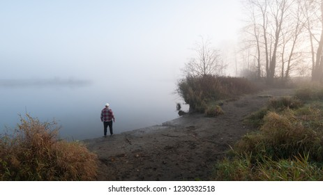 Man standing on river bank looking into the fog at sunrise.