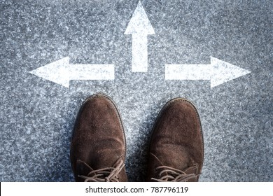 man standing on road with three direction arrow choices, left, right or move forward