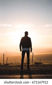 Man standing on road watching sunrise