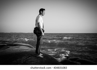Man standing on rock looking at sea,Black and white