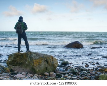 Man standing on rock in the middle of ocean.  Tourist stand alone on a rock and watching sea horizon within sunset