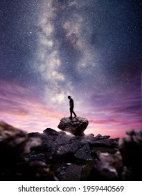 A man standing on A rock as the milky way galaxy rises into the night sky at dusk. Photo composite