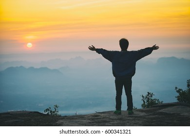 A man standing on the rock in the morning with sunrise and mountain.
