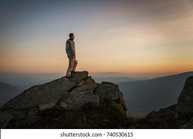Man standing on rock on mountain top at sunset