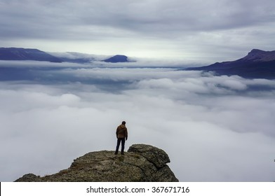 Man standing on rock's edge above the clouds