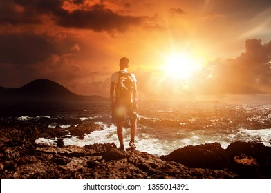 Man standing on rocks watching a dramatic orange sunrise on a cloudy day over a rough ocean with white surf and waves